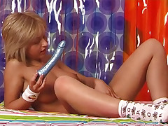 A bare light-haired teenager is laying on her back on a bed. She is holding a hitachi that she thrusts against her nipples. She stretches her legs, moving her vagina in the direction of the camera and touches her clit.